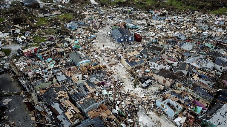 Image: People walk through a neighbor destroyed by Hurricane Dorian at Marsh Harbour in Great Abaco Island, Bahamas