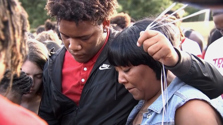 Image: Dashaud Williams and his mother, Razel Sheppard, mourn the death of his twin brother, Deshaud, at a memorial in Lewisville, Texas.