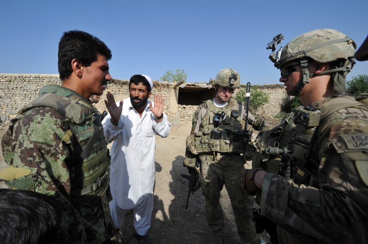 Image: An Afghan soldier (L) serves an interpre