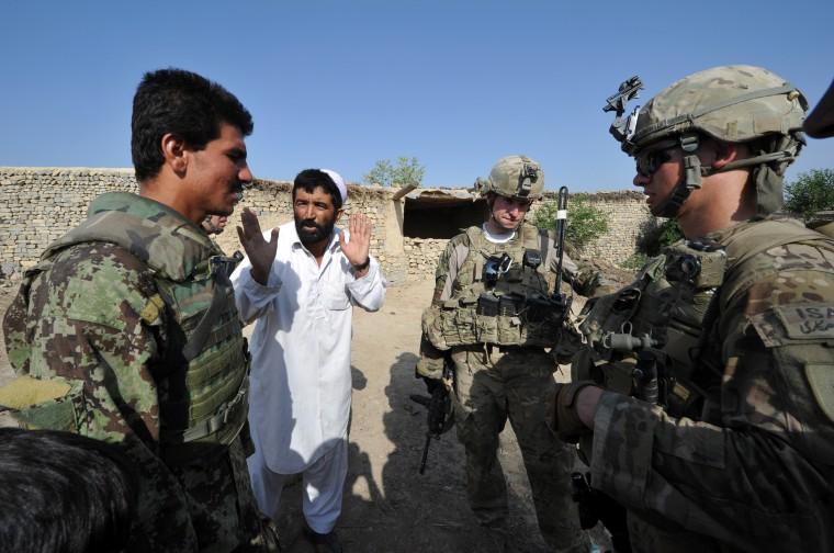 Image: An Afghan soldier (L) serves an interpre