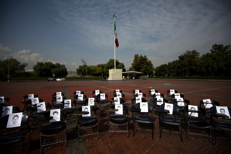 Image: Photographs of 43 missing students from Ayotzinapa sit on school desks in the UNAM plaza in Mexico City in 2014.