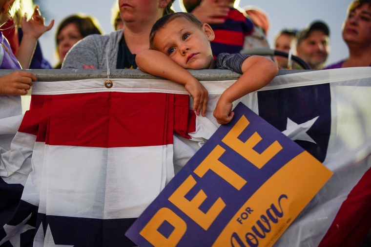 Image: A young boy holds a campaign placard as Pete Buttigieg, South Bend Mayor and Democratic presidential hopeful, speaks at a campaign event in Dubuque