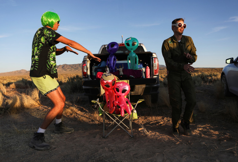 Image: Two men dance on a road to an entrance to Area 51 in Rachel, Nevada