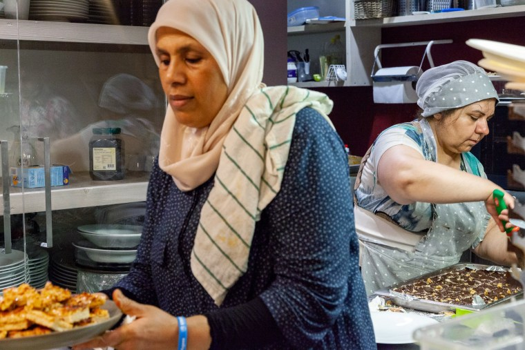 Kholoud Marei, left, and Maryam Khoshluie prepare Middle Eastern sweets to go with tea and other hot drinks during one of the community's events held at Orient Experience.