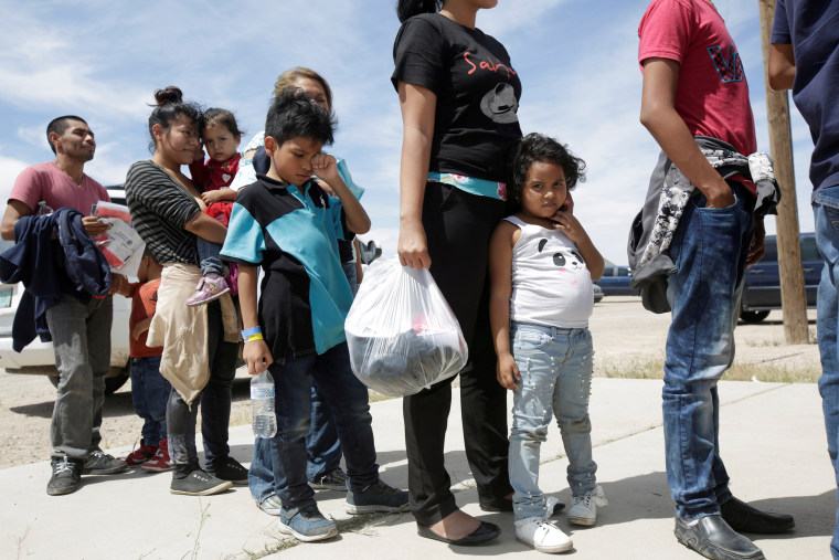 Image: Central American migrants stand in line before entering a temporary shelter, after illegally crossing the border between Mexico and the U.S., in Deming