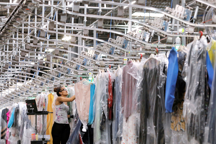 """Image: A woman works in the automated sortation section at Rent the Runway's \""""Dream Fulfillment Center\"""" in Secaucus, New Jersey"""
