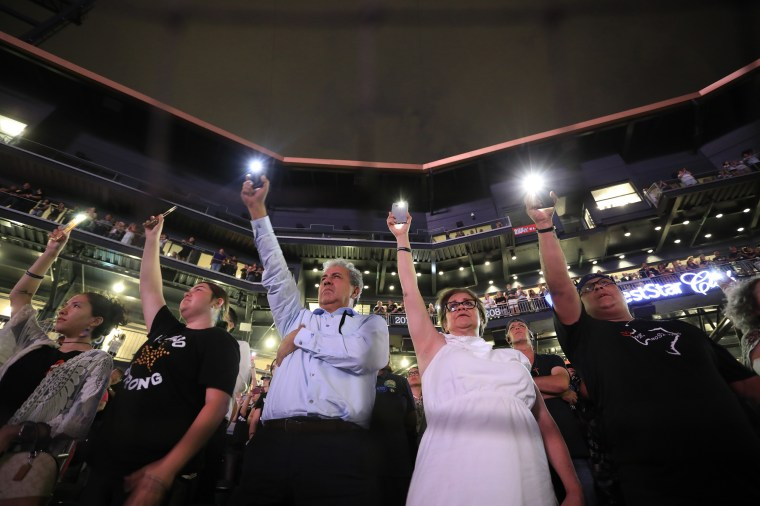 People hold up their cellphones as the names of the victims of the Aug. 3 mass shooting are read during a memorial service on in El Paso, Texas, on Aug. 14, 2019.