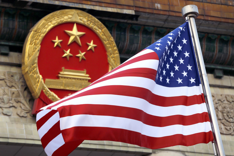 An American flag is flown next to the Chinese national emblem outside the Great Hall of the People in Beijing on Nov. 9, 2017.