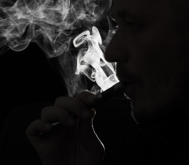 Close up photo of a person vaping e-cigarette