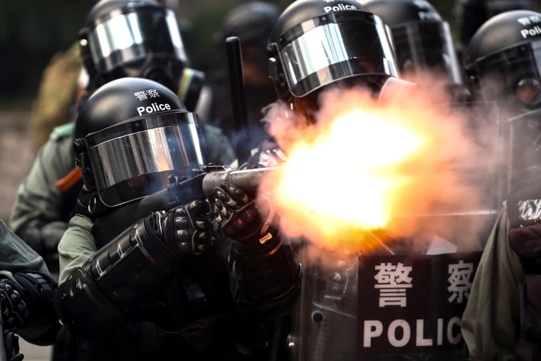 Image: A riot police fires tear gas to disperse anti-government protesters after a march in Hong Kong