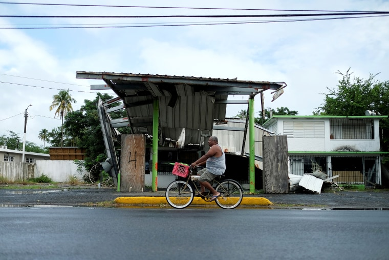 Image: A man rides his bicycle past a gas station that was damaged by Hurricane Maria two years ago, as Tropical Storm Karen approaches in Loiza