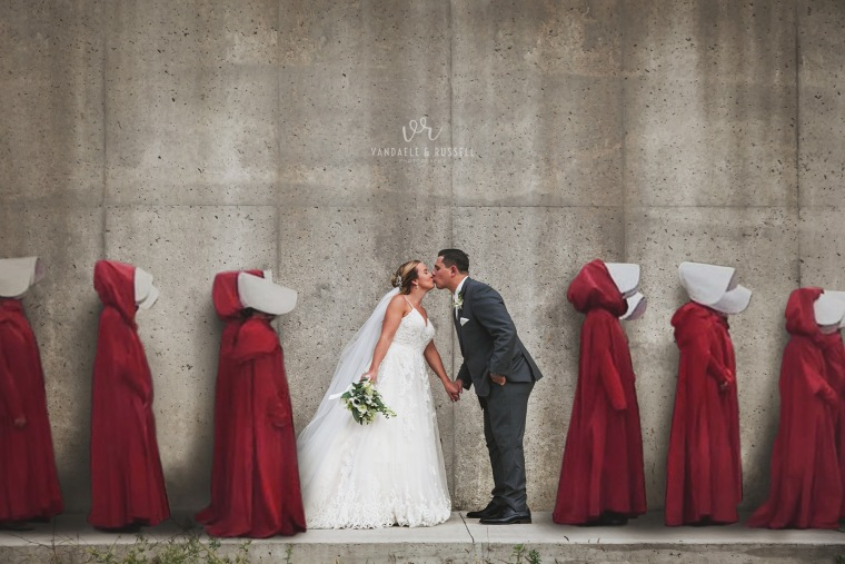 """A bride and groom pose for their wedding photo in front of the """"hanging wall"""" from the Hulu series """"The Handmaid's Tale"""" in Cambridge, Mass. The photo was digitally altered to include characters from the popular series."""