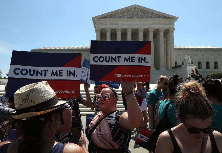 "Protesters hold ""Count Me In"" signs in front of the U.S. Supreme Court"