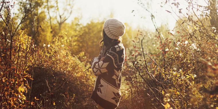 Woman in sweater walking in autumn forest
