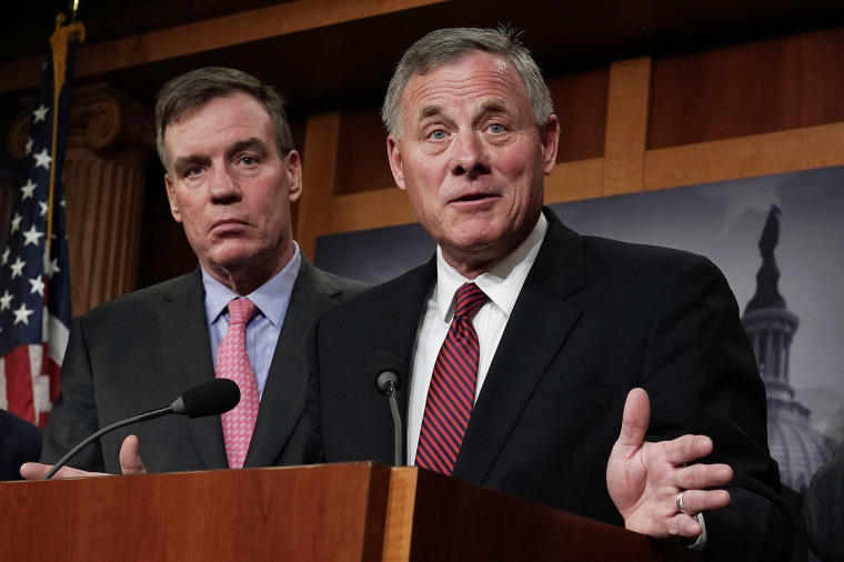 Chairman of the Senate Intelligence Committee Sen. Richard Burr speaks as committee Vice Chairman Sen. Mark Warner listens during a news conference at the Capitol on March 20, 2018.