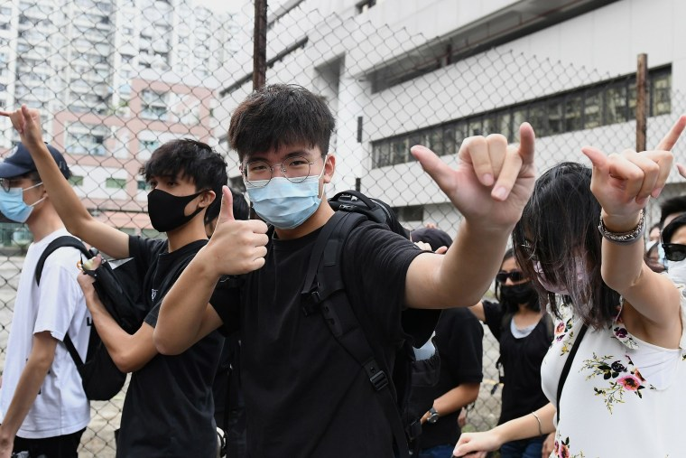 Image: A young man gestures as protesters gather outside the Eastern District Courts in Hong Kong