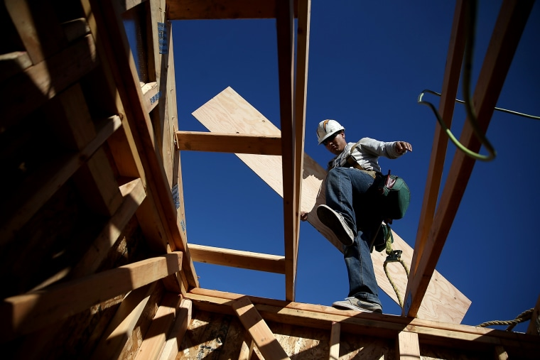 Image: A worker carries lumber while building a house in Petaluma, Calif., in 2015.