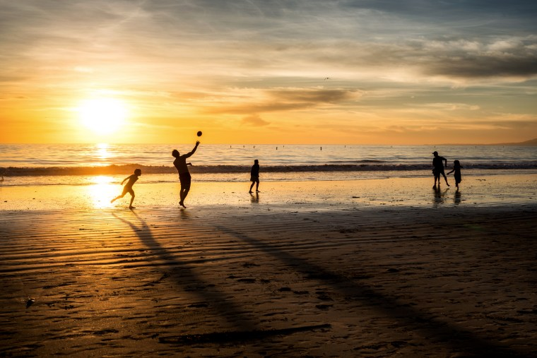 Image: Silhouettes of a family with kids playing football in sunset light on Santa Monica beach.