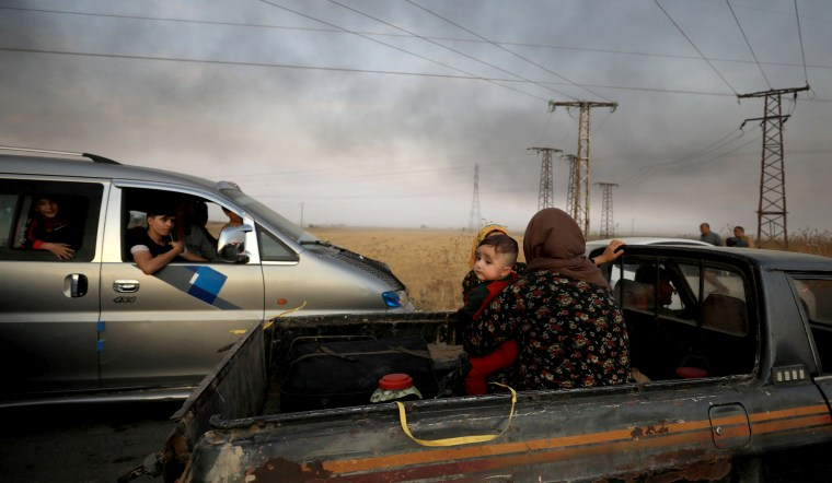 Image: A woman and her baby sit in the back of a truck as they flee Ras al-Ain, Syria, on Oct. 9, 2019.