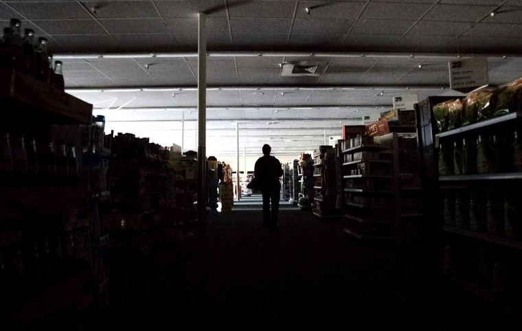 Image: Shift supervisor James Quinn walks through a darkened CVS Pharmacy in downtown Sonoma, Calif., during a power cut on Oct. 9, 2019.