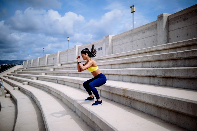 Image: Athletic woman with smartwatch listening to music and doing jump squats on urban stadium stands