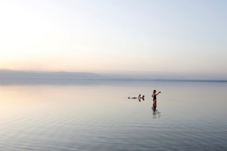 Image: People take a swim on the shores of the Dead Sea near Amman