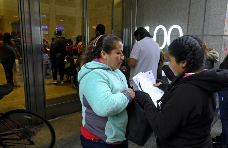 Two women look over their documents by a line snaking around the block outside a U.S. immigration office with numerous courtrooms on Jan. 31, 2019, in San Francisco.