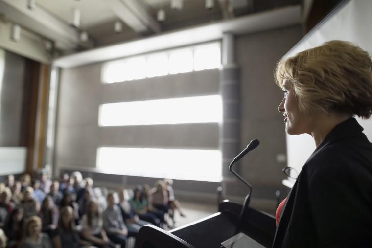 Professor speaking at podium to auditorium audience