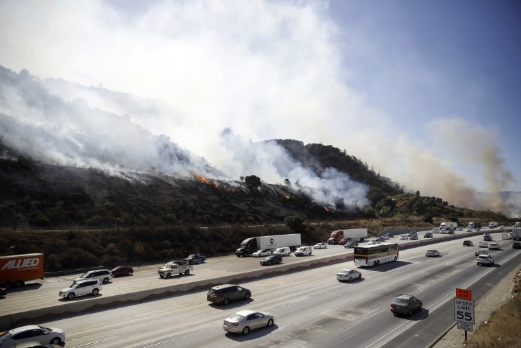 Image: Smoke from a wildfire spreads across the hillside as traffic flows along the I-5 Freeway in Newhall, Calif., on Oct. 12, 2019.