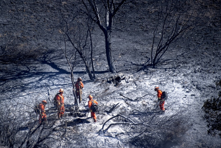 Image: Firefighters extinguish hot spots in Porter Ranch, outside of Los Angeles, on Oct. 12, 2019.
