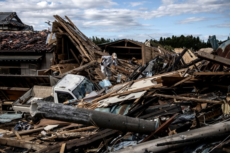 Image: A man looks through debris of a building that was destroyed by a tornado shortly before the arrival of Typhoon Hagibis in Chiba, Japan, on Oct. 13, 2019.