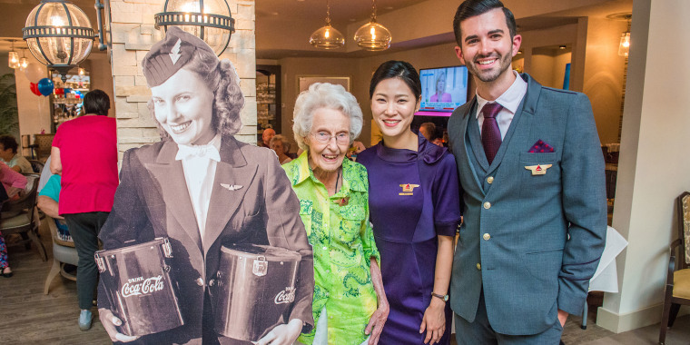 Former flight attendant Sybil Peacock Harmon (center) posed with a photo of herself from 1940 and two of Delta's flight attendants last year.