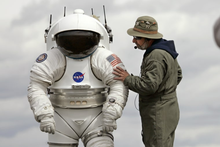Technician Bill Welch, left, stands inside a 300-pound space suit as another technician talks with him June 10, 2008, in Moses Lake, Wash.  NASA scientists and contractors spent two weeks in Moses Lake field testing some of the vehicles and robots that will be used when humans return to the moon later this century. (AP Photo/Elaine Thompson)