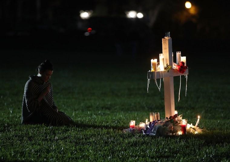 Former Douglas student, Rachelle Borges, sits near a candlelit cross during a vigil.