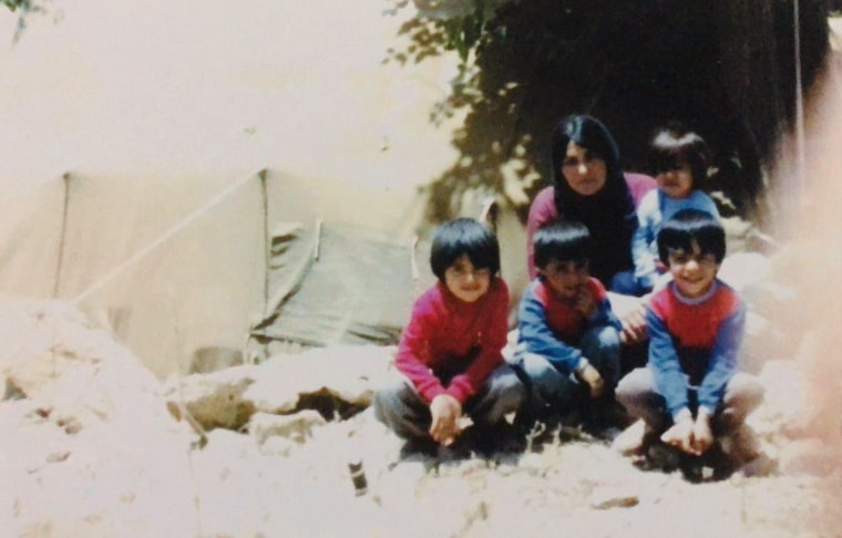 Yerevan Adham, left, is shown with his mother and three brothers at a refugee camp in Iran in 1987.