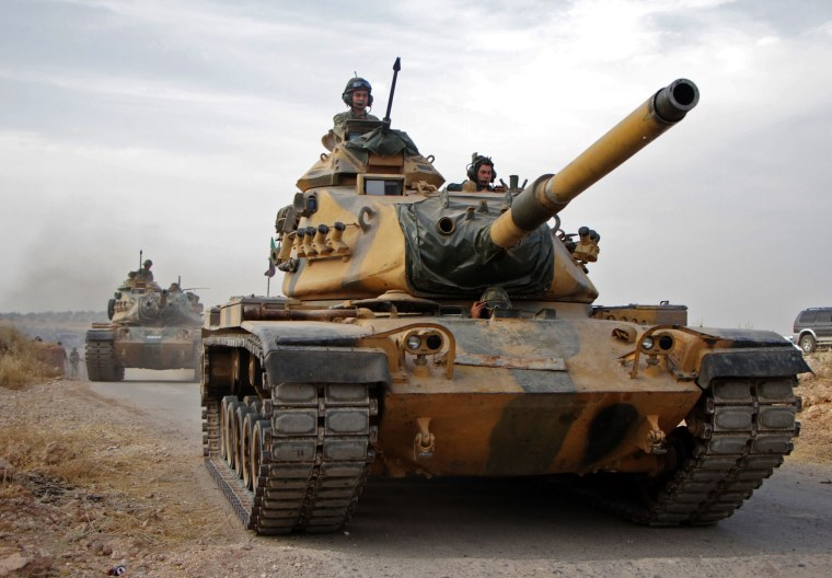 Image: Turkish soldiers with US-made M60 tanks drive through the town of Tukhar, north of Syria's northern city of Manbij