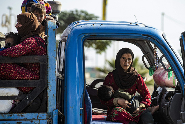 Image: Syrian families fleeing the battle zone between Turkey-led forces and Kurdish fighters from the Syrian Democratic Forces (SDF) in and around the northern flashpoint town of Ras al-Ain, arrive in the city of Tal Tamr