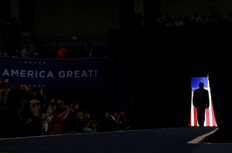 Image: President Donald Trump is silhouetted against a U.S. flag as he holds a campaign rally in Lake Charles, Louisiana
