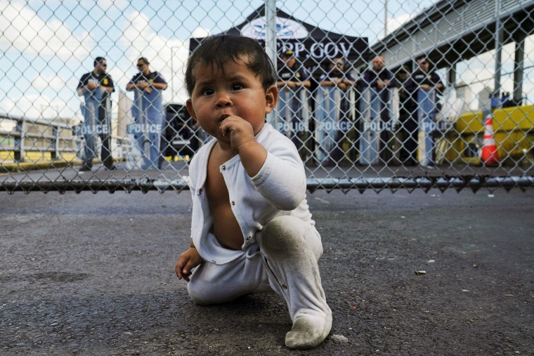 Image: A Mexican baby is seen in front of the gates to the Gateway International Bridge in Matamoros