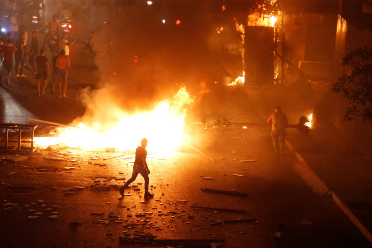 Image: A demonstrator walks close to a fire during a protest over deteriorating economic situation in Beirut