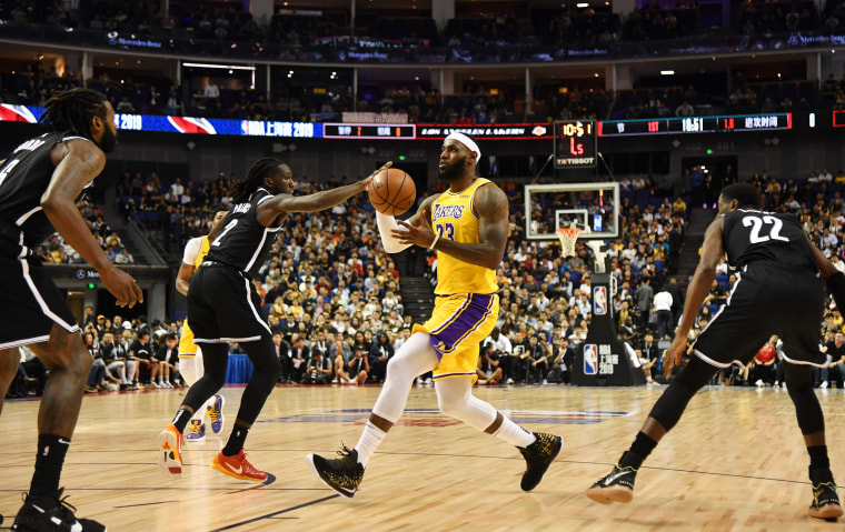 Image: LeBron James of the Los Angeles Lakers drives past Brooklyn Nets players during the National Basketball Association pre-season game between the LA Lakers and Brooklyn Nets at the Mercedes Benz Arena in Shanghai
