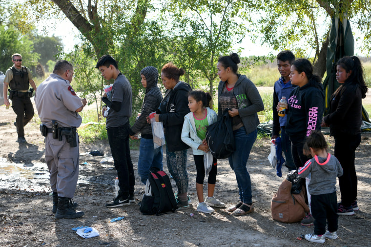 Image: Central American asylum seekers who illegally crossed the Rio Grande nearby wait to be processed after turning themselves in to U.S. Border Patrol in Los Ebanos