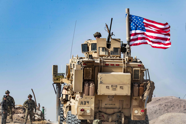 Image: A U.S. soldier sits atop an armoured vehicle during a demonstration by Syrian Kurds against Turkish threats at a US-led international coalition base on the outskirts of Ras al-Ain town in Syria's Hasakeh province near the Turkish border