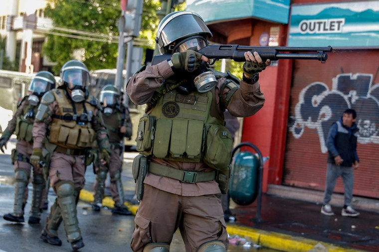 Image: A riot policeman shoots at demonstrators during protests in Valparaiso, Chile
