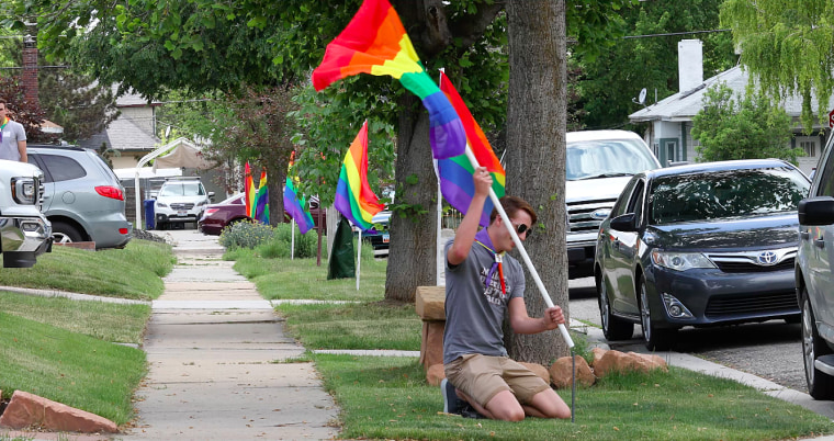 Project Rainbow volunteer Nick Kiahtipes plants rainbow flags in Salt Lake City in June 2018.