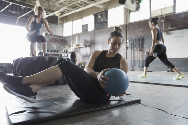 Image: Focused, strong woman doing seated medicine ball twist in gritty gym
