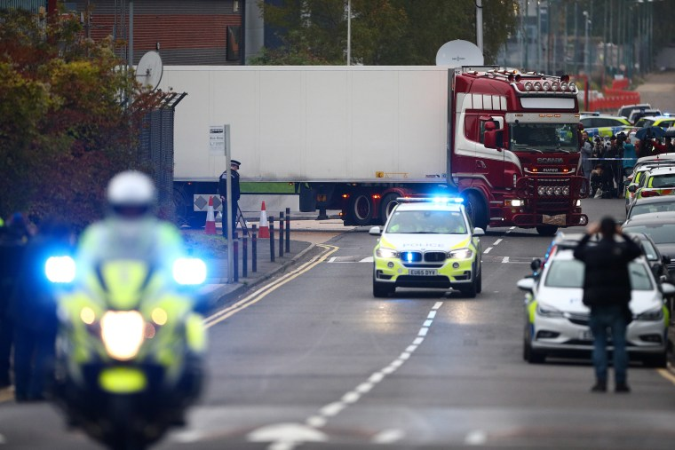 Image: Police officers drive away a lorry in which 39 dead bodies were discovered sparking a murder investigation at Waterglade Industrial Park in Grays, Essex