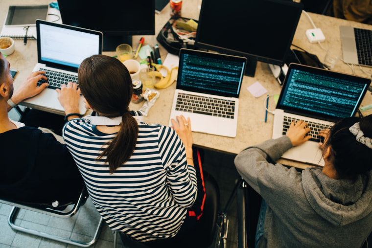High angle view of young multi-ethnic computer programmers coding on laptops at desk in small office