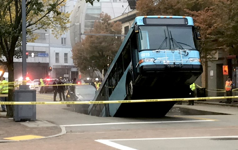 Image: Authorities secure the scene after a Port Authority bus fell through a sinkhole in Pittsburgh on Oct. 28, 2019.