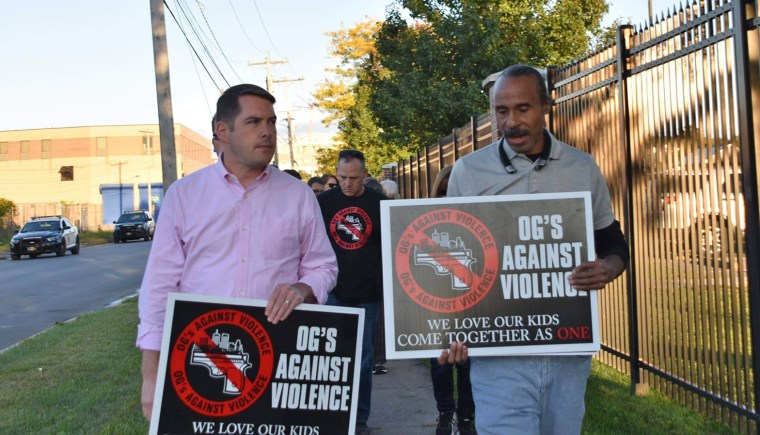 Anti-violence advocate Clifford Ryans, right, walks with Syracuse Mayor Ben Walsh during a demonstration.